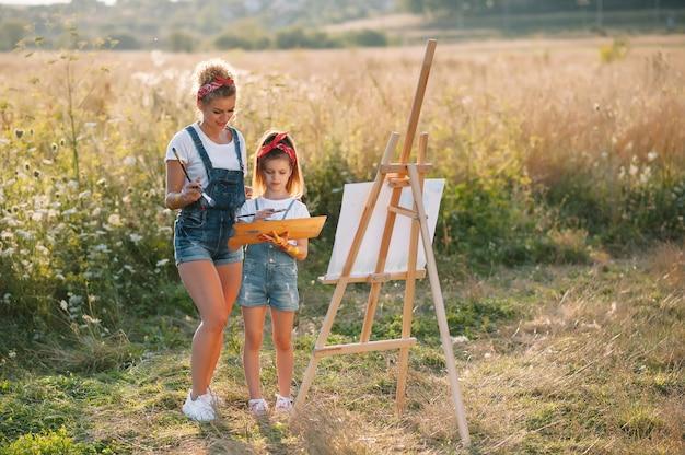 Beauté mère peindre avec sa petite fille. femme élégante, dessiner l'image avec une petite fille. enfant mignon dans un t-shirt blanc et un jean bleu.