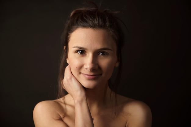 Beauté mode portrait femmes avec une peau naturelle parfaite et de beaux cheveux bien entretenus, taillés en queue. grand portrait en studio sur fond noir