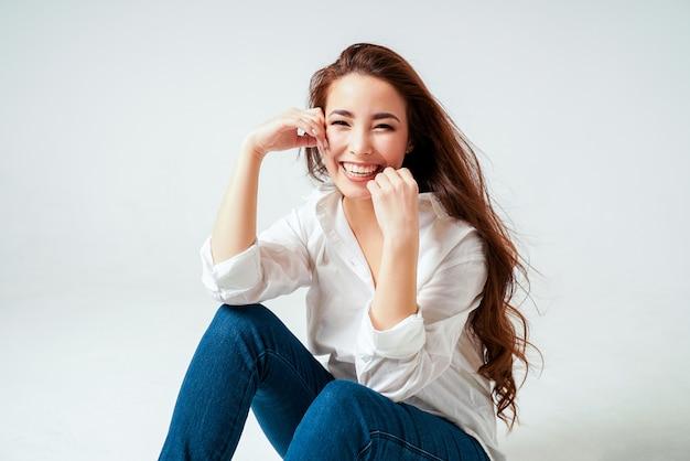 Beauté mode portrait de souriant sensuelle jeune femme asiatique avec de longs cheveux noirs en chemise blanche sur blanc