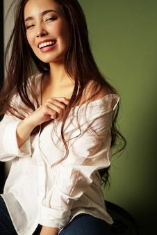 Beauté mode portrait de souriant sexy jeune femme asiatique sensuelle avec de longs cheveux noirs en chemise blanche