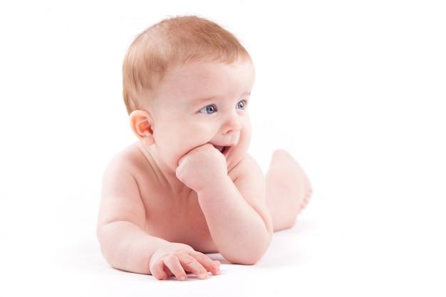 Beauté petit garçon en couche blanche se trouve sur le ventre