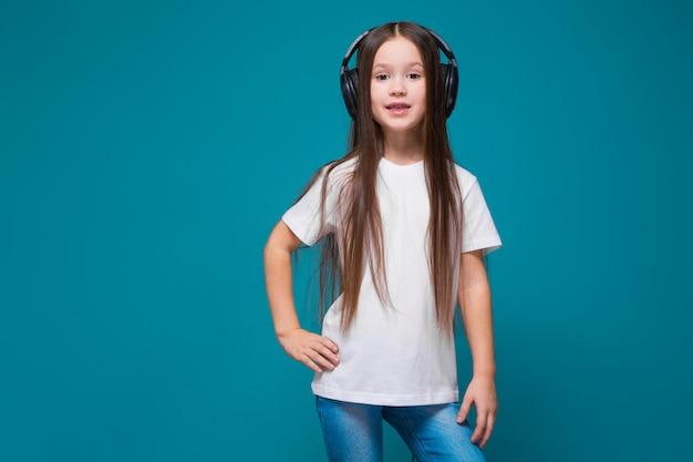 Beauté petite fille en tee-shirt et écouteurs aux cheveux longs