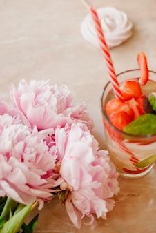 Beauté plat poser avec de l'eau de fraise désintoxication, accessoires et pivoines sur un fond de marbre