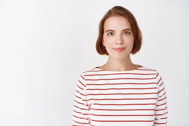 Beauté. portrait d'une jeune femme confiante avec une peau du visage de lumière naturelle, sourire tendrement, debout en blouse rayée contre un mur blanc
