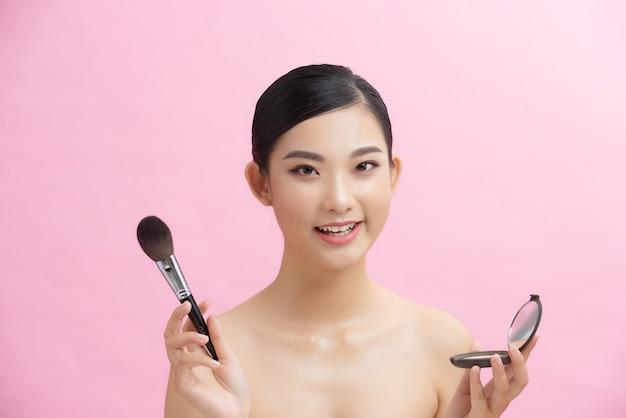 Beauté professionnelle de belle femme asiatique appliquant le maquillage cosmétique de maquillage.