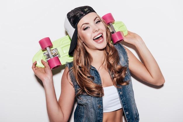 Beauté rieuse. joyeuse jeune femme tenant une planche à roulettes colorée et exprimant sa positivité en se tenant debout sur fond blanc