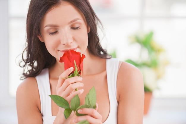 Beauté à la rose. gros plan image de belle jeune femme tenant une rose rouge près du visage et souriant alors qu'il était assis dans son lit
