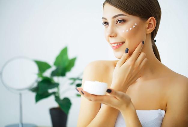 Beauté et soins. jeune femme avec de la crème pour le visage dans les mains. morni