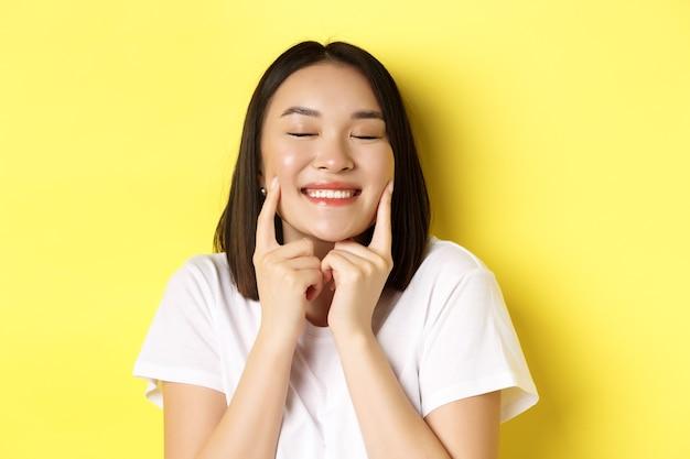 Beauté et soins de la peau. gros plan d'une jeune femme asiatique aux cheveux noirs courts, une peau saine et éclatante, souriant et touchant les fossettes sur les joues, debout sur le jaune.