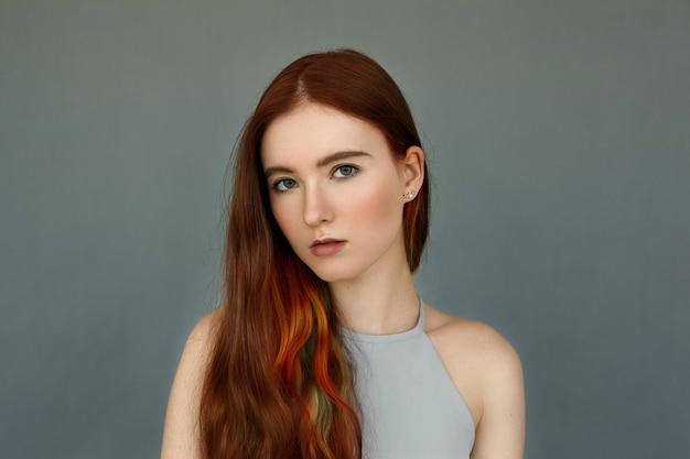 Beauté, soins de la peau, jeunesse, style et mode. superbe modèle de jeune femme tendre avec de longs cheveux bouclés de couleur flamme avec des reflets debout isolé au mur gris blanc, à la recherche