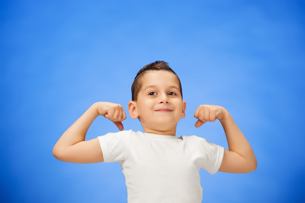Beauté souriant sport enfant garçon montrant ses biceps