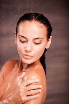 Beauté sous la douche. belle jeune femme torse nu debout dans la douche et se lavant l'épaule
