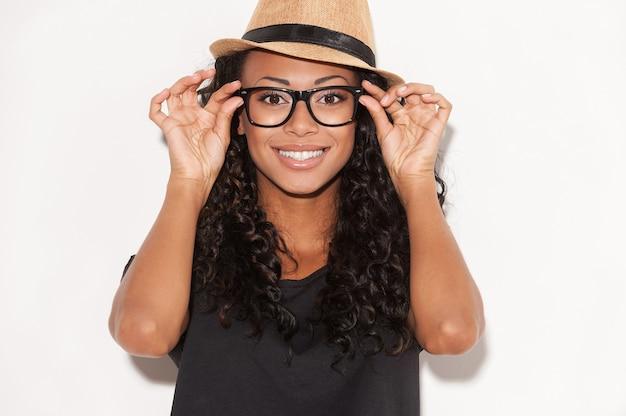 Beauté de style génial. portrait de la belle jeune femme africaine à lunettes et chapeau funky ajustant ses lunettes et souriant en se tenant debout sur fond blanc
