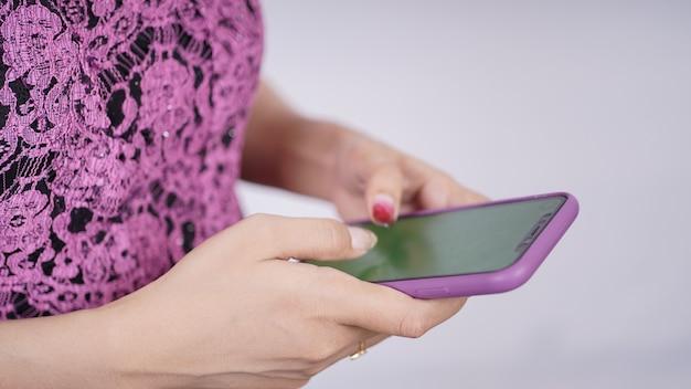 Beauté en violet kebaya jouant au téléphone mobile isolé sur fond blanc