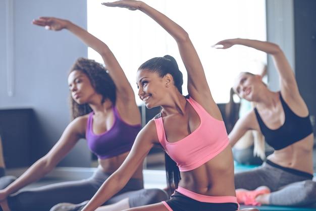 Beautés flexibles. jeunes belles jeunes femmes avec des corps parfaits en vêtements de sport faisant des étirements avec le sourire au gymnase
