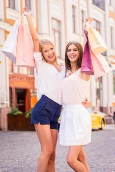 Beautés avec des sacs à provisions. deux jeunes femmes attirantes tenant des sacs à provisions et souriant tout en se tenant à l'extérieur