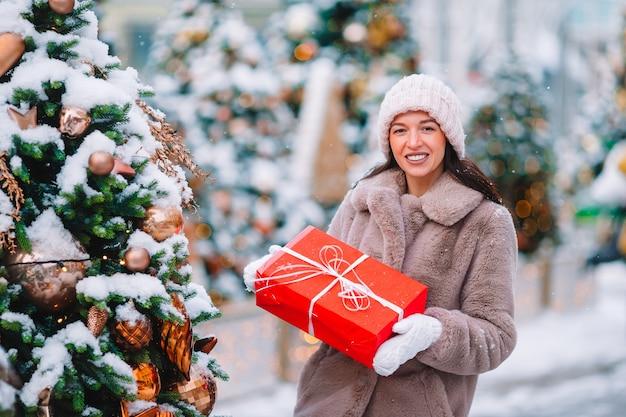 Beautidul femme près de l'arbre de noël dans la neige à l'extérieur