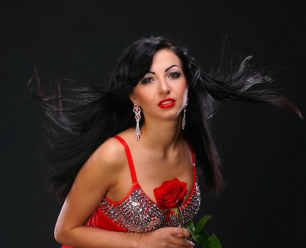 Beautifil jeune femme avec une rose sur fond sombre
