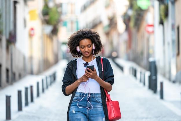 Beautiful afro american girl écouter de la musique sur un casque à l'extérieur.