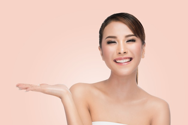 Beautiful spa girl montrant la paume de la main ouverte vide pour texte sur rose avec un tracé de détourage