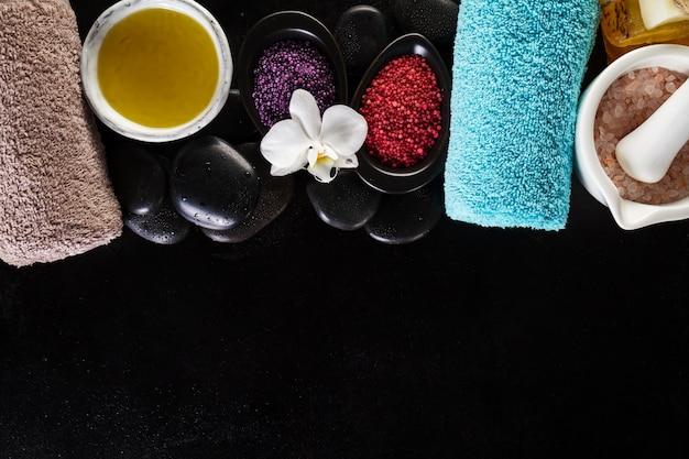 Beautiful spa set produits spa avec des huiles essentielles, du savon, des serviettes, du sel de mer spa sur un fond humide foncé. horizontal avec espace de copie.
