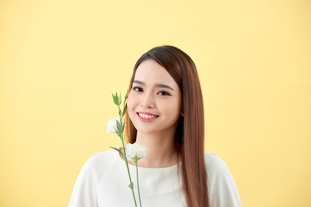 Beauty portrait of lady 20s holding white lisianthus fleurs sur fond jaune