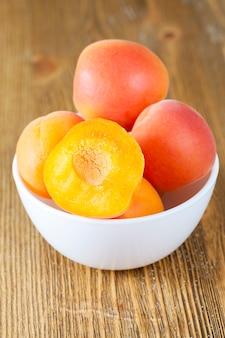 Beaux abricots mûrs et juteux frais dans un bol sur une table, gros plan