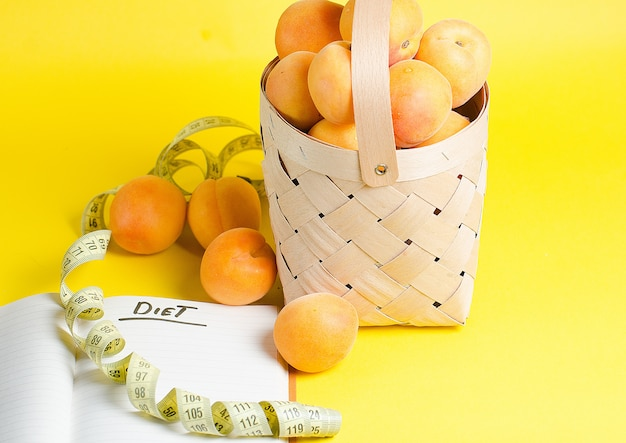 De beaux abricots mûrs se trouvent dans un panier en bois sur un mur jaune