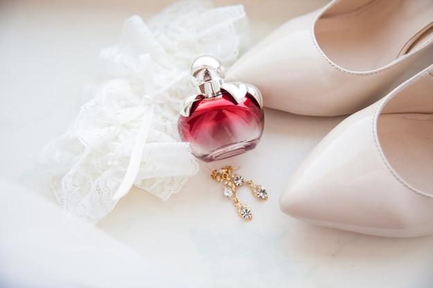 Beaux accessoires de mariage. chaussures de mariée, parfums sur un voile blanc