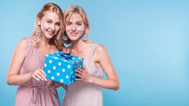 Beaux amis tenant une boîte cadeau