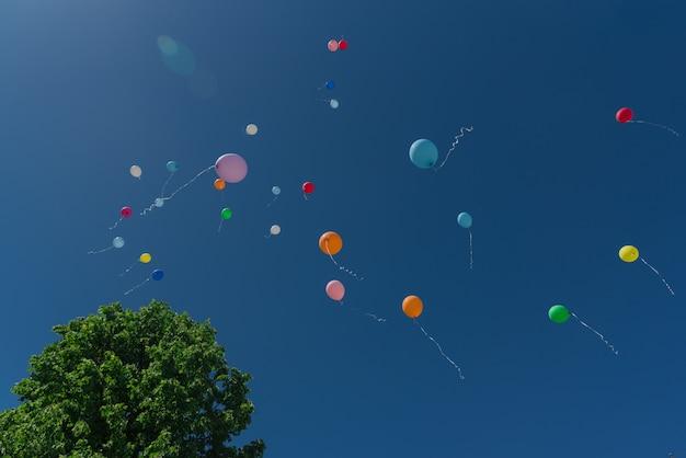 Beaux ballons multicolores contre le ciel