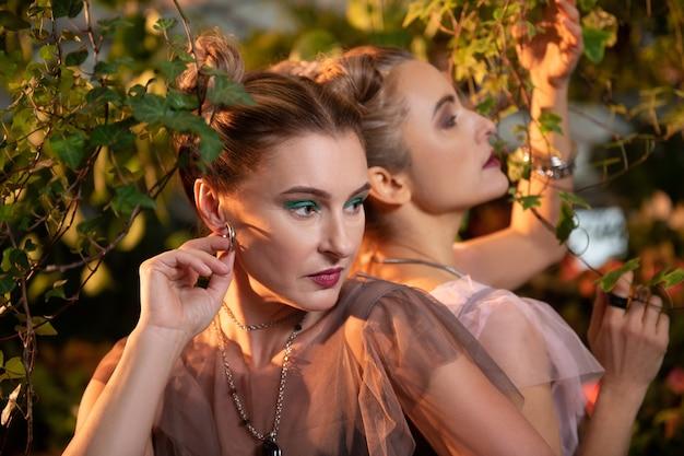 De beaux bijoux. belle femme agréable touchant sa boucle d'oreille en posant