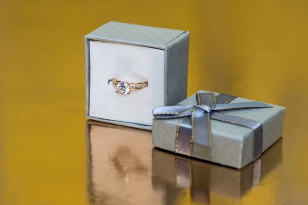 Beaux bijoux en or dans une boîte cadeau sur fond doré