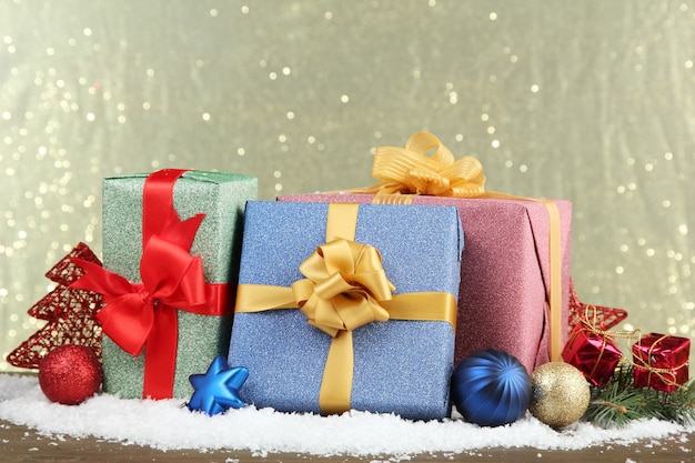 Beaux cadeaux lumineux et décor de noël, sur fond brillant