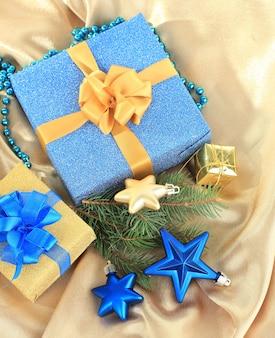 Beaux cadeaux lumineux et décor de noël, sur tissu de soie
