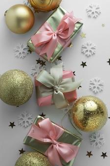 Beaux cadeaux or boules gloden sur blanc. noël, fête, fond d'anniversaire. célébrez le fond des boîtes surprise brillantes. vue de dessus de plat créatif.