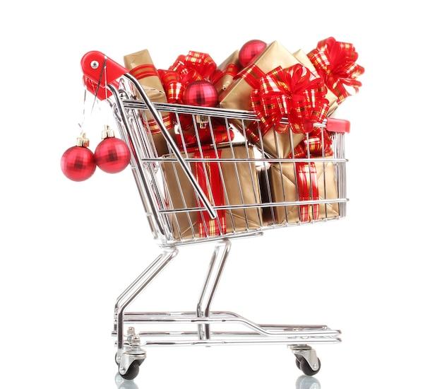Beaux cadeaux d'or avec le ruban rouge et les boules de noël dans le caddie d'isolement sur le blanc