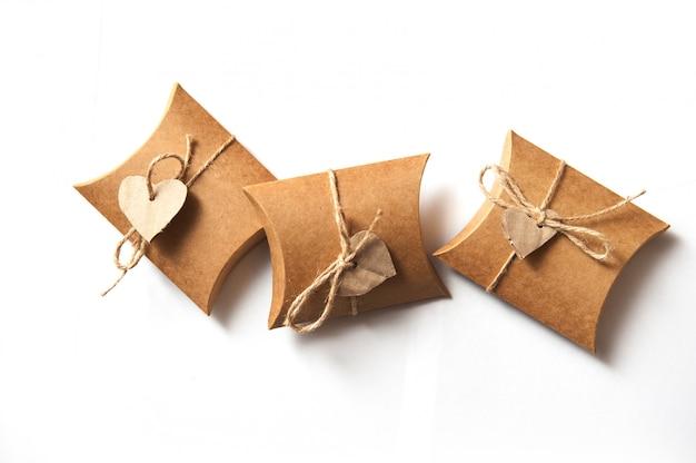 Beaux cadeaux de papier kraft avec un coeur sur blanc