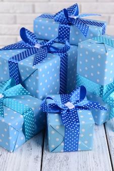 Beaux cadeaux sur table sur fond de mur de briques