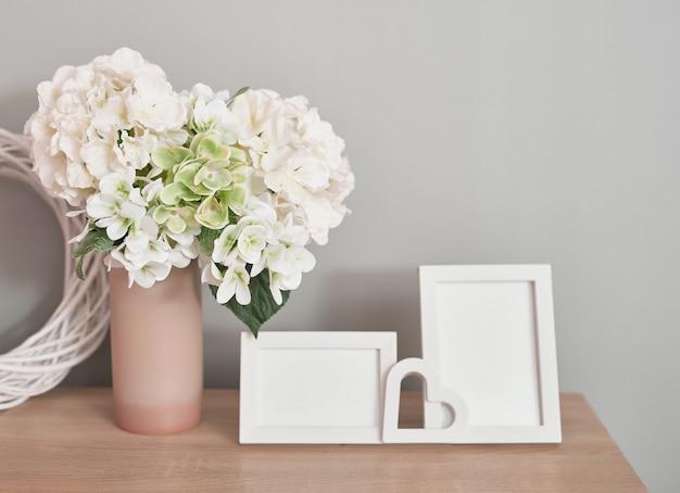 Beaux cadres photo blancs sur table avec bouquet de fleurs blanches