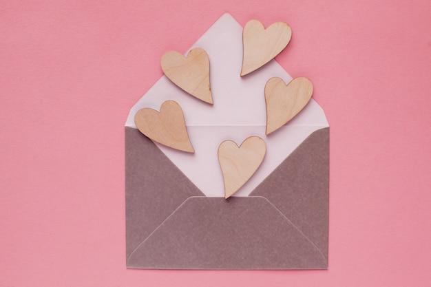 Beaux coeurs en bois dans une enveloppe en papier