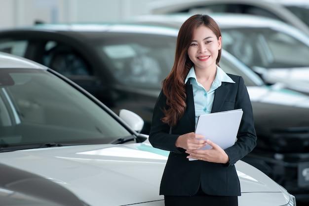 Les beaux concessionnaires automobiles asiatiques sont heureux de vendre de nouvelles voitures dans la salle d'exposition et de vendre des voitures.