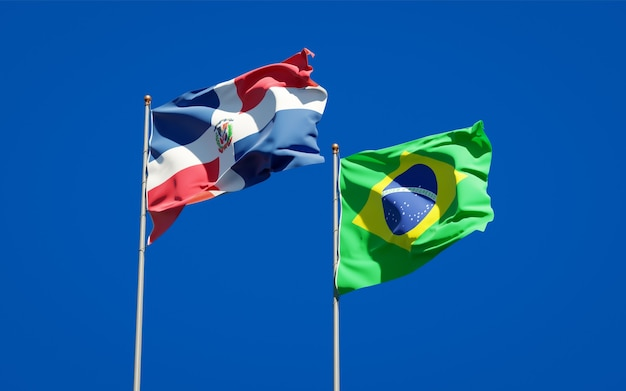 Beaux drapeaux d'état national du brésil et de la république dominicaine ensemble sur ciel bleu