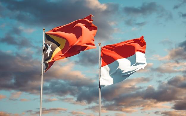 Beaux drapeaux d'état national du timor oriental et de l'indonésie ensemble sur ciel bleu