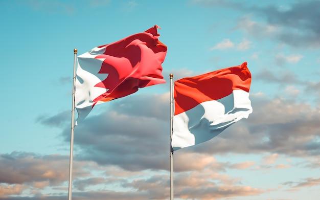 Beaux drapeaux d'état national de l'indonésie et de bahreïn ensemble sur ciel bleu