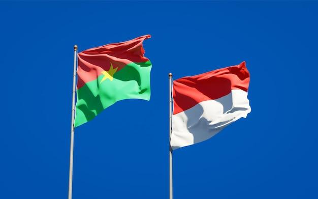 Beaux drapeaux d'état national de l'indonésie et du burkina faso ensemble sur ciel bleu