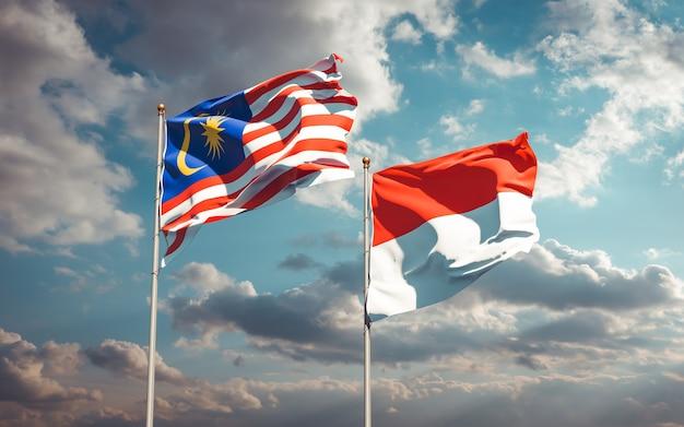 Beaux drapeaux d'état national de la malaisie et de l'indonésie ensemble sur ciel bleu