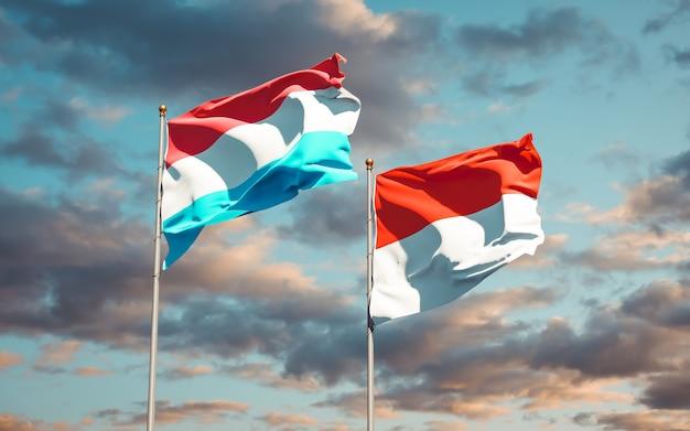 Beaux drapeaux des états nationaux du luxembourg et de l'indonésie ensemble sur ciel bleu