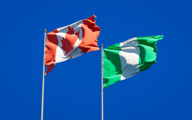 Beaux drapeaux des états nationaux du nigéria et du canada ensemble sur ciel bleu