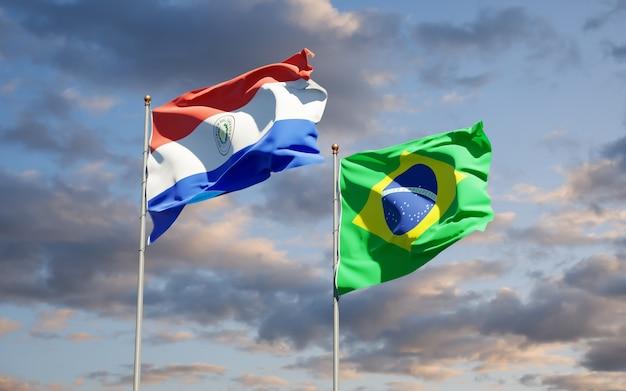 Beaux drapeaux des états nationaux du paraguay et du brésil ensemble sur ciel bleu